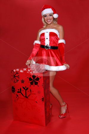 Mrs. Santa's Christmas Bag stock photo, Sexy Mrs Santa standing beside a large bag full of christmas gifts by Robert Deal