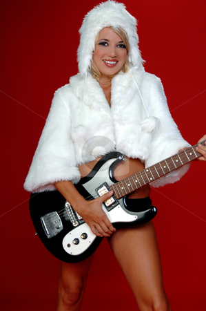 Rock N Roll  Snow Bunny stock photo, Blond snow bunny in a white furry coat and hat and black hot pants over a red background with an electric guitar by Robert Deal