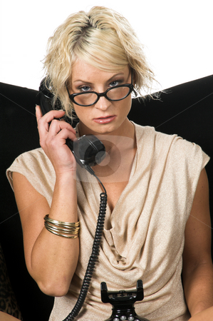 Blond On A Retro Phone stock photo, Pretty blonde with short hair and a nice smile wearing glasses and a metallic tan cowel neck dresssitting on a black and lepoard couch talking on a retro phone by Robert Deal