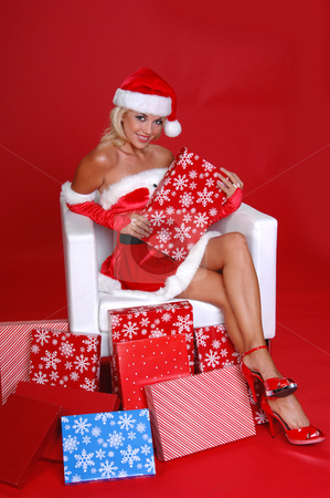 Santa's Helper stock photo, Sexy Mrs Santa Clause sitting in a snow white chair surrounded by Christmas gifts by Robert Deal
