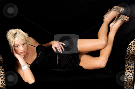 Pretty Blond Laying On Couch stock photo, Pretty blonde fashion model with short blond hair laying on her side on a black and lepoard print couch by Robert Deal