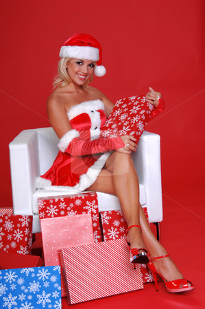 Santa's Helper stock photo, Sexy Mrs Santa Clause holding a package and sitting in a snow white chair surrounded by Christmas gifts by Robert Deal