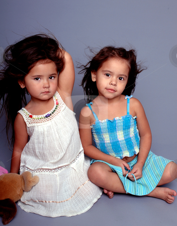 Little Fashion Models stock photo, Two little girls sitting together on a grey background and playing model. One girl holding a stuffed toy by Robert Deal