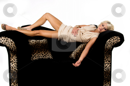 Pretty Blond Laying On Couch stock photo, Pretty blonde with short hair and a nice smile wearing a metallic tan cowel neck dress laying across the back of a black and lepoard print couch by Robert Deal