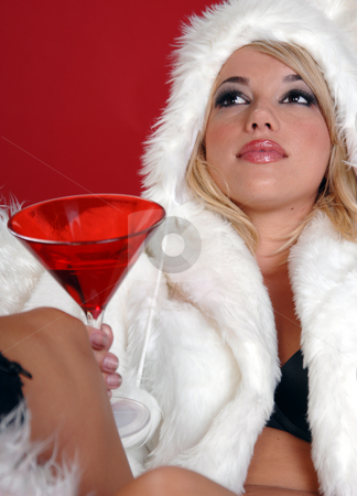Fuzzy Snow Bunny stock photo, Sexy blond snow bunny in a white furry coat and hat and black hot pants over a red background reclined with a martini by Robert Deal
