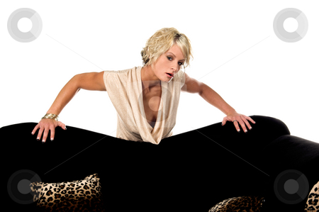 Pretty Blonde Behind Couch stock photo, Pretty blonde with short hair and a nice smile wearing a metallic tan cowel neck dress standing behind a couch with her arms outstretched. by Robert Deal