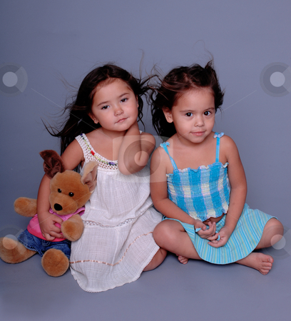 Mini Models stock photo, Two little girls sitting together on a grey background and playing model. One girl holding a stuffed toy by Robert Deal
