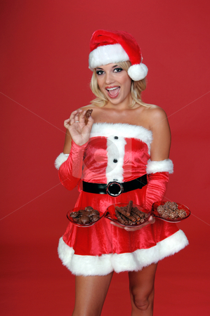 Christmas Chocolates stock photo, Sexy Mrs Santa serves up a tray of Christmas Chocolates half body on red background by Robert Deal