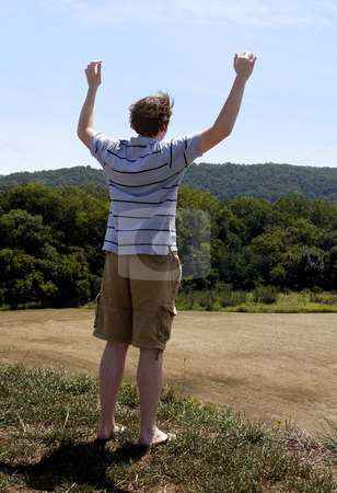 Man rejoicing stock photo, Young man with outstretched arms on top of a mountain looking over the valley by Anita Peppers