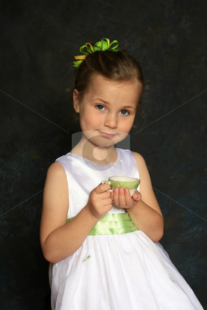 Tea party stock photo, Cute little girl in a white dress holding a tea cup by Anita Peppers