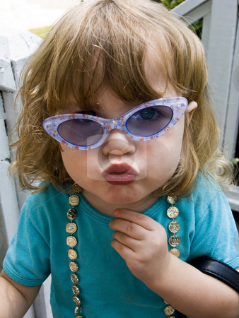 Kiss stock photo, Cute little girl in crooked sunglasses giving a kiss by Anita Peppers