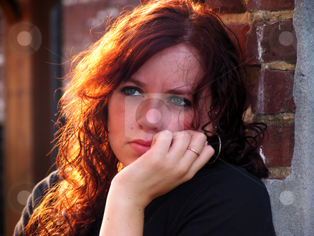 Sadness stock photo, Portrait of a young woman with sunlit hair and sad expression by Anita Peppers
