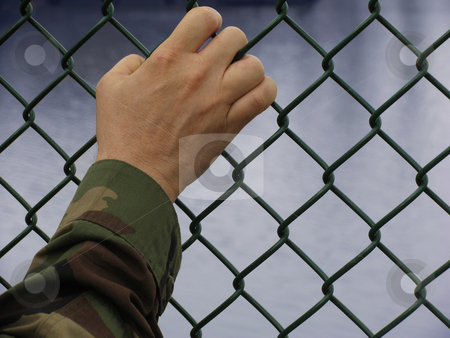 Deployed stock photo, Soldier's hand resting on a fence by Anita Peppers