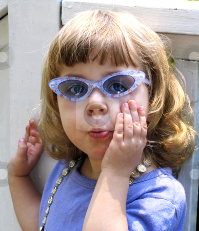 Girl in sunglasses stock photo, Little girl wearing sunglasses and expression by Anita Peppers