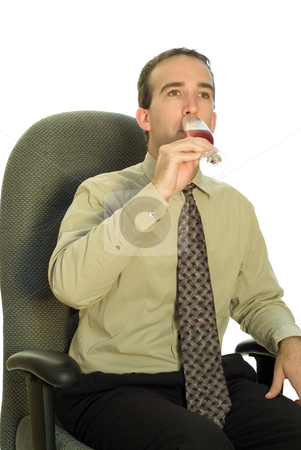 Businessman Drinking Wine stock photo, A young businessman drinking red wine while sitting in his chair by Richard Nelson