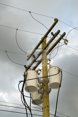 Powerline Transformers stock photo, Low angle view of a set of power line transformers, shot against a cloudy sky by Richard Nelson
