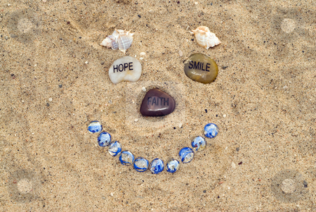 Face In The Sand stock photo, A happy face made with stones and seashells by Richard Nelson