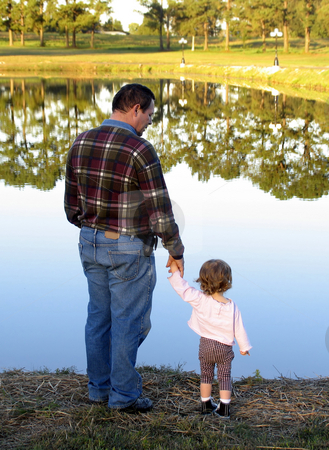 Looking at mirror lake stock photo, Father and daughter looking at beautiful reflective lake by Anita Peppers