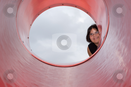 Girl Peeking stock photo, A young girl peeking into the opening of a round slide by Richard Nelson
