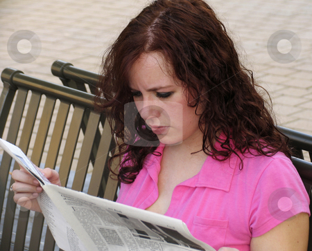 Young woman reading newspaper stock photo, Young woman reading a newspaper in a park by Anita Peppers