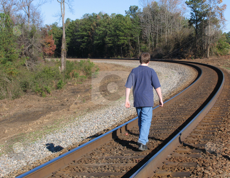 Boy on tracks stock photo, Teen boy walking on train tracks by Anita Peppers