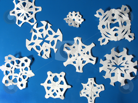 Snowflakes stock photo, Children's paper snowflake cut-outs against a blue background by Anita Peppers