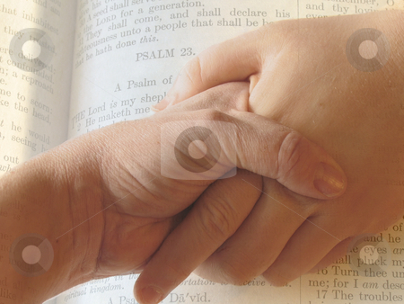 Hands stock photo, Hands clasped in front of a bible page by Anita Peppers