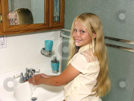 Child washing hands stock photo, Smiling girl washing her hands in a bathroom sink by Anita Peppers