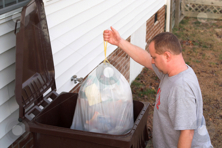Garbage Man stock photo, A man emptying his refuse into a garbage can. by Robert Byron