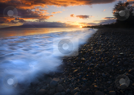 Cobblestone Sunset stock photo, A last bit of sunset light kisses the cobblestones of astretch of beach near Lahaina on Maui. Lanai is partially hidden under a cloud in the distance. by Mike Dawson