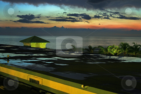 Sunset after Rain, with Ocean stock photo, A sunset reflected in the puddles on a building, with view of the ocean. by Lucy Clark