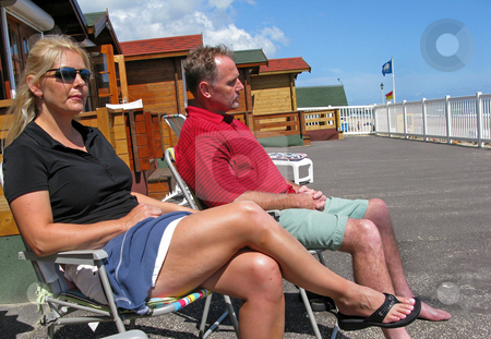 Relaxation stock photo, A couple relaxing near the beach. by Lucy Clark