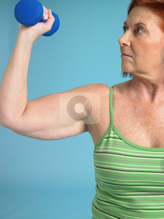 Woman with dumbbell exercising stock photo, Senior woman lifting a dumbbell by Mpixis World