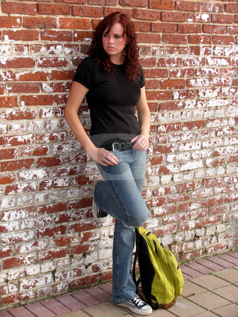 Waiting stock photo, Young woman standing against a brick wall by Anita Peppers