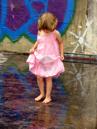Reflections stock photo, Little girl playing in puddles with graffiti reflected by Anita Peppers
