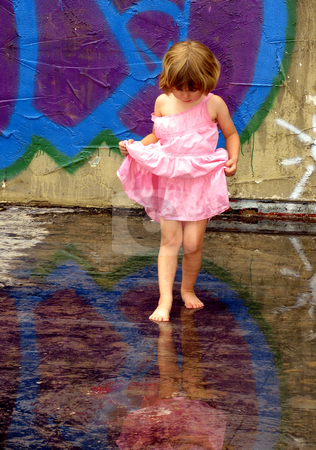 Reflections 2 stock photo, Little girl playing in rain puddles with reflections by Anita Peppers