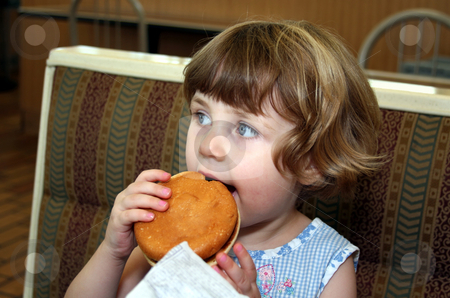 Hamburger girl stock photo, Little girl eating hamburger in fast food restaurant by Anita Peppers