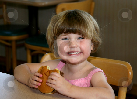 Girl eating hamburger stock photo, Girl eating hamburger in fast-food restaurant by Anita Peppers