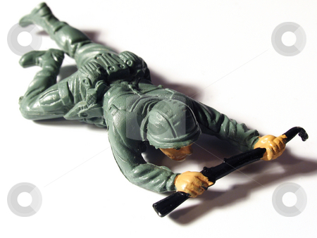 Toy soldier crawling stock photo, Plastic toy army soldier crawling by Anita Peppers