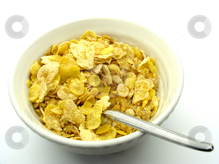 Cereal in bowl stock photo, Cereal flakse in bowl with spoon by Anita Peppers