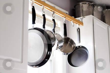 Pots and Pans stock photo, Pots and pans hanging over a kitchen sink. by Robert Byron