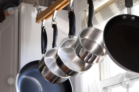 Pots and Pans stock photo, Pots and Pans hanging on a rack in a kitchen. by Robert Byron