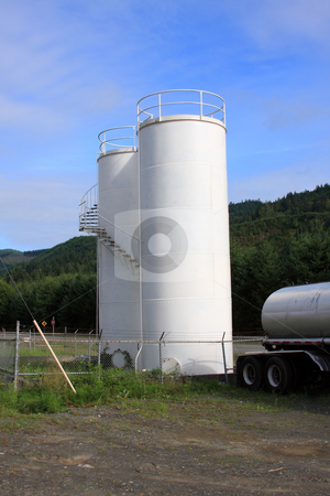 Gasoline Storage Tanks. stock photo, A pair of gas tanks, white with blue sky. by Steve Stedman