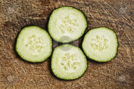 Slices of cucumber on a wooden background. stock photo, Slices of cucumber on a wooden background. by Pablo Caridad