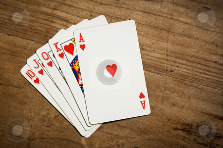 Royal flush poker hand stock photo, Royal flush poker hand on an old scratched table with copy space. Hearts. by Pablo Caridad