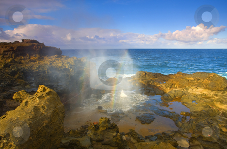 Creating Miracles stock photo, Nakalele Blowhole truly a miracle of nature. A shelf of lava rock on the north shore of Maui eroded by the punishing sea until the waves created a vent that spews like a geyser off and on and when the llight of late afternoon hits the spray the miracle of rainbow color becomes apparent. by Mike Dawson