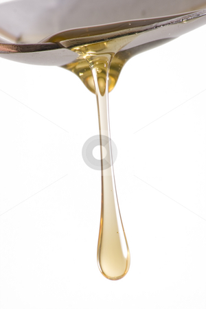 Honey Drip From Spoon stock photo, Honey dripping from spoon isolated on white background with plenty of copy space by Mike Dykstra