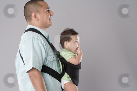 Man carrying baby in pouch stock photo, Father with baby in a baby carrier by Mpixis World