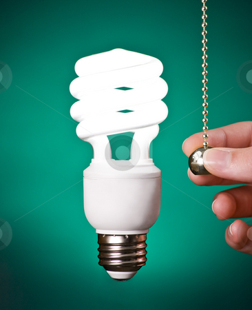 Compact Fluorescent Light Bulb Switched On stock photo, Compact Fluorescent Light Bulb Switched On With Hand on Green Background by Mike Dykstra