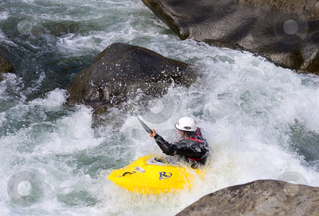 Single kayaker in whitewater stock photo, A kayaker taking bit of spray in the face while negotiating some rapids between two large bouldera along the Wenatchee River by Mike Dawson
